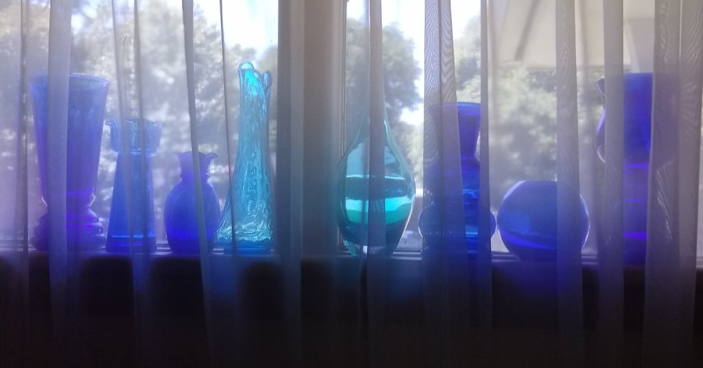 Backlit row of blue glass vases in a windowsill